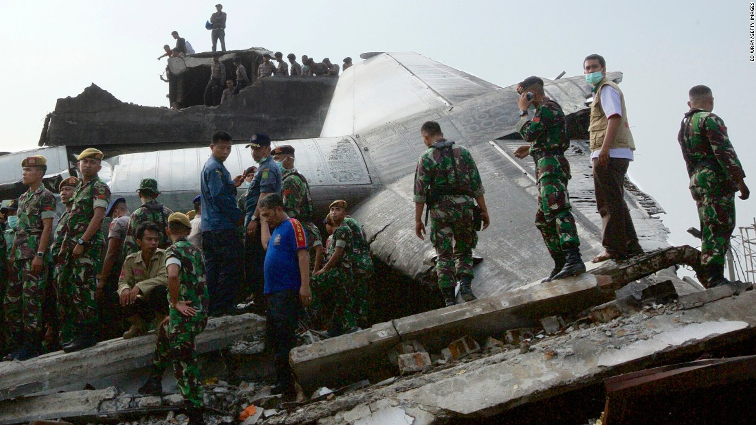 Search and rescue personnel comb through the wreckage of the plane.