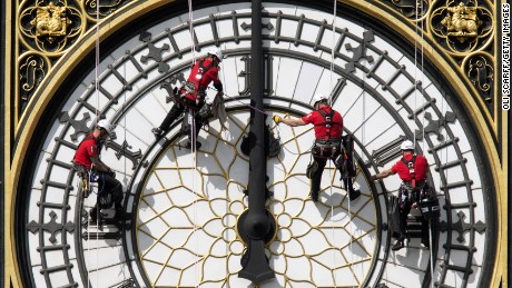 Workers clean the East-facing clock face of Big Ben at the Houses of Parliament in August 2014 in London.
