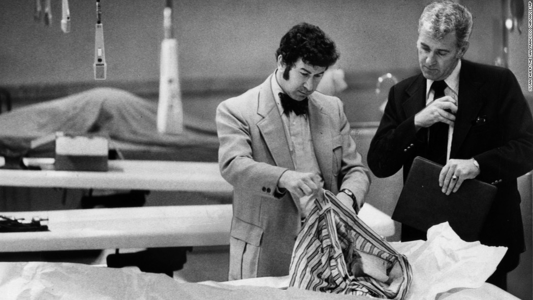 "Homicide inspectors David Toschi, left, and William Armstrong go through a ""Zodiac Killer"" victim's clothes looking for clues. ""In the '70s there was a certain kind of killer who had the skill to get away with murder long enough to assemble the body count where they would be classified as serial killers,"" said James Alan Fox, the author of ""Mass Killing."" The Zodiac Killer has never been caught.<br />"