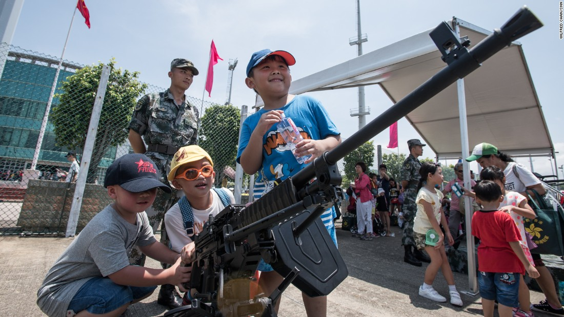 Soldiers watch as children play with machine guns -- not loaded, of course.