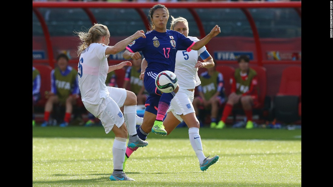 Yuki Ogimi of Japan battles through two England defenders.