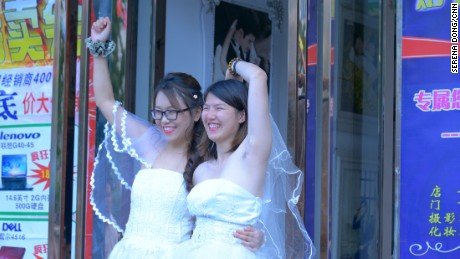Teresa Xu, left, and Li Tingting, right, share a moment outside a beauty salon, where the two were preparing for their wedding.