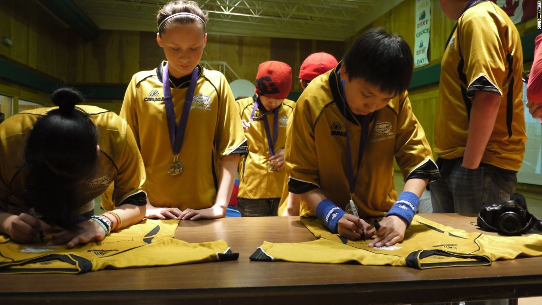 Fort Liard players sign commemorative jerseys, to be mounted on the walls of their school, following victory at a tournament in the neighboring town of Fort Simpson, almost 200 miles north.