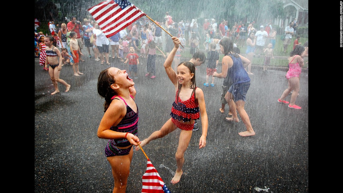 Cousins Ann Claire Schenkel, left, and Greer Shenkel dance around Aurora Circle in the spray of a fire hose after a July Fourth parade in Memphis, Tennessee, on Saturday.