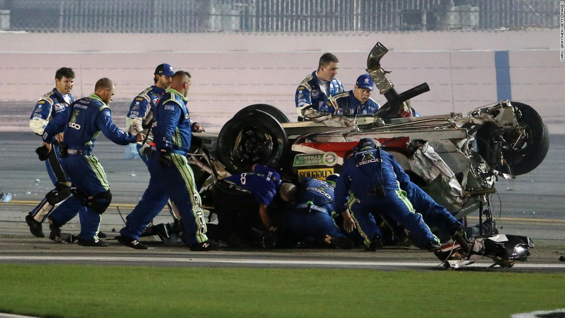 Crew members rush to check on Dillon after his car stopped rolling.