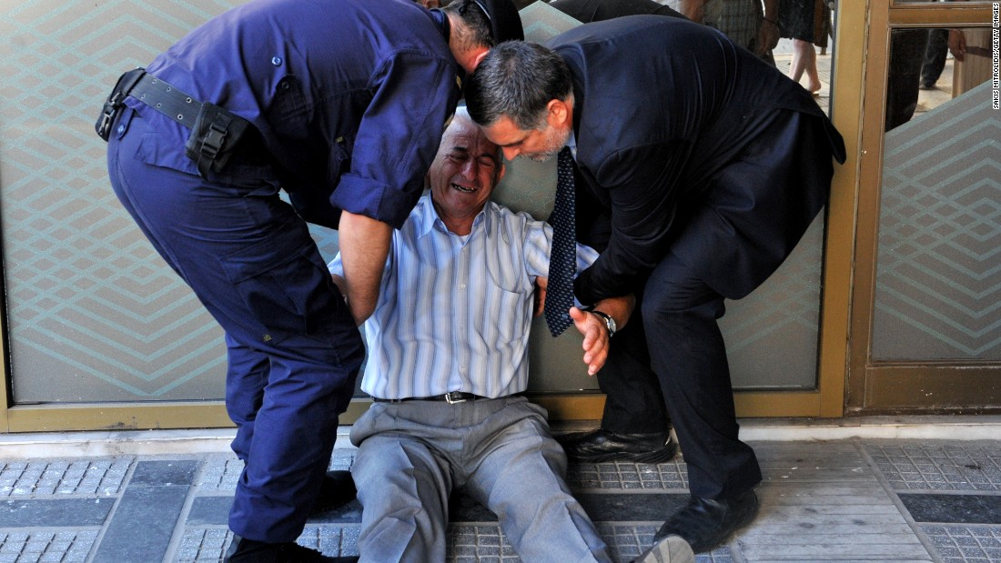 An crying elderly man is assisted by an employee and a policeman outside a national bank branch as pensioners queue to get their pensions, with a limit of 120 euros.