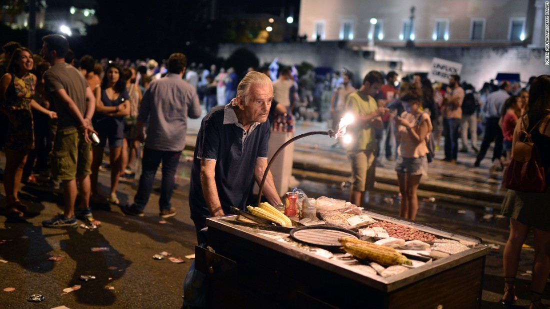 An elderly man pushes a cart with corn for sale as people celebrate the victory of the 'no' campaign in front of the parliament.