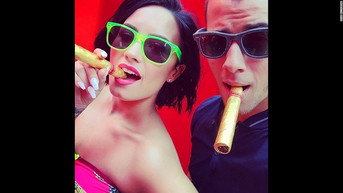 "Singers Demi Lovato and Nick Jonas pose with 24-karat gold cigars in this selfie Lovato <a href=""https://instagram.com/p/4r5ItAuKnv/"" target=""_blank"">posted to Instagram</a> on Friday, July 3. ""Nothing like one of your business partners/best friends showing up to support me and to celebrate #COOLFORTHESUMMER!!!!!!"" Lovato said, referring to her latest single."