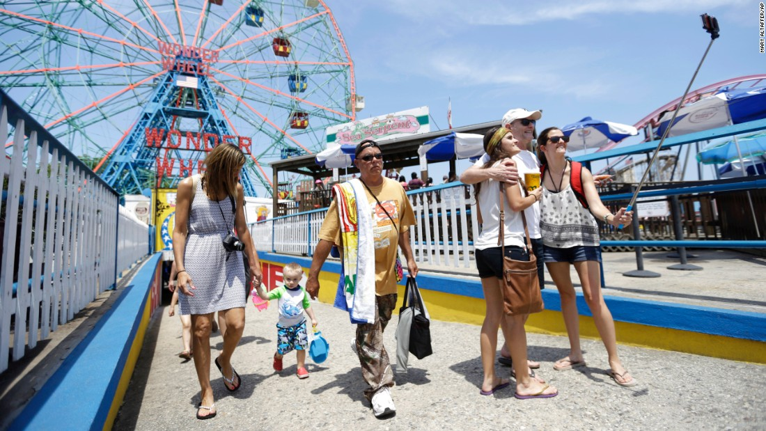 "Coney Island visitors use a selfie stick Friday, July 3, in New York City. <a href=""http://www.cnn.com/2015/07/01/living/gallery/selfies-look-at-me-0701/index.html"" target=""_blank"">See 27 selfies from last week </a>"