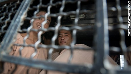 Myanmar nationals Win Zaw Tun and Zaw Lin look out from a prison transport van as they arrive at court for the start of their trial on the Thai resort island of Koh Samui on July 8, 2015.