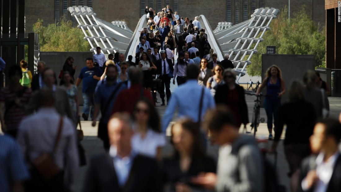 People walk across the Millennium Bridge in London on July 9. Some 4 million journeys are typically made on the Underground each day, so when the system is down, the city comes close to grinding to a halt.
