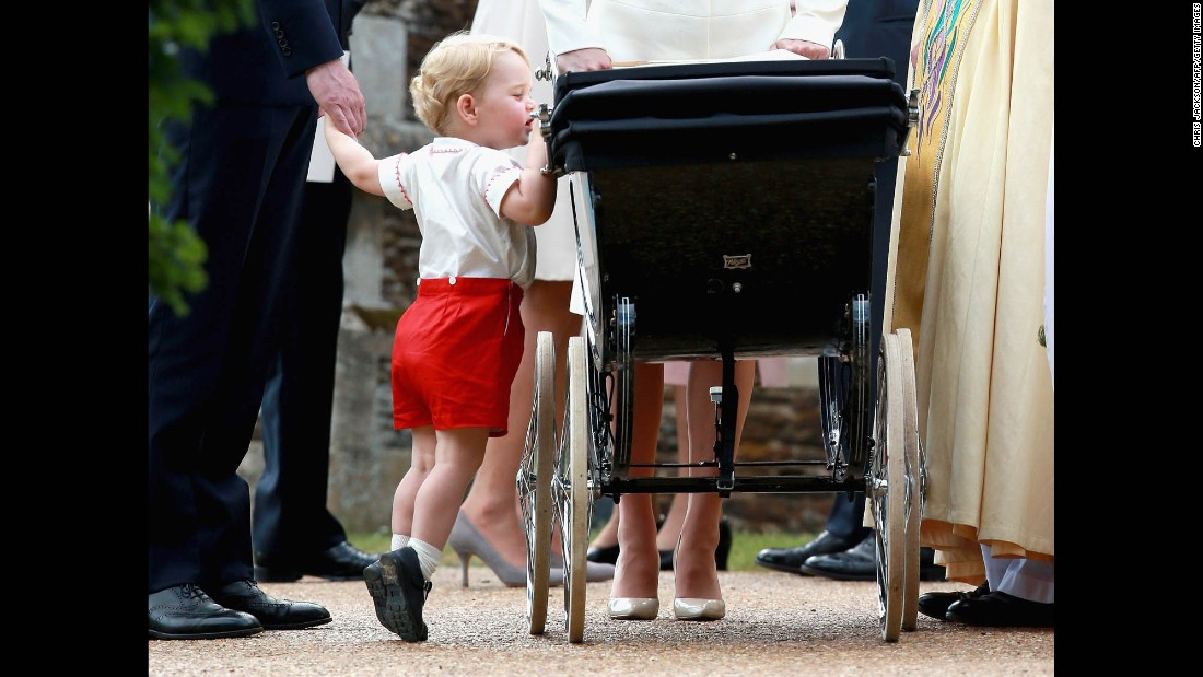 Prince George peers into the stroller of his younger sister, Princess Charlotte, following her christening on July 5, 2015.