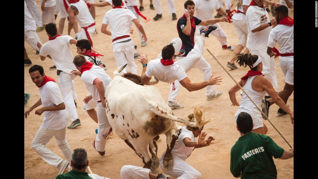 "A man goes airborne Wednesday, July 8, during the annual ""running of the bulls"" in Pamplona, Spain."