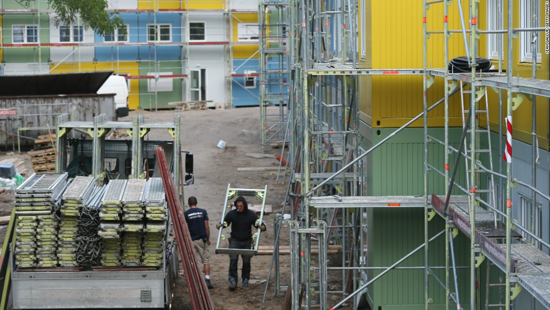 Workers construct a container facility in Berlin's Zehlendorf district that will house refugees and asylum applicants on July 9. The wars in Syria and Iraq, as well as crises and economic desperation in Africa and the Balkans, have contributed to the rising tide of refugees entering Germany.