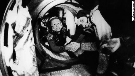 Commander of the Soviet crew of Soyuz Alexei Leonov, left, and commander of the American crew of Apollo Thomas Stafford shake hands in space after the Apollo and Soyuz spacecrafts docked on July 17, 1975.