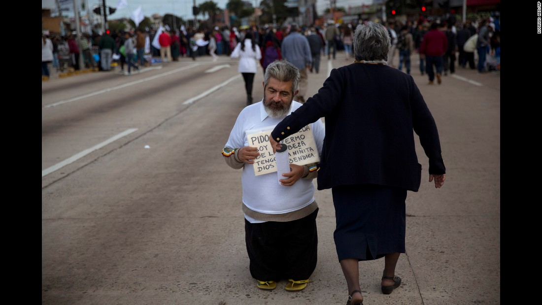 A beggar asks for donations near a site in Santa Cruz where people were gathering to see the Pope pass by on July 9.