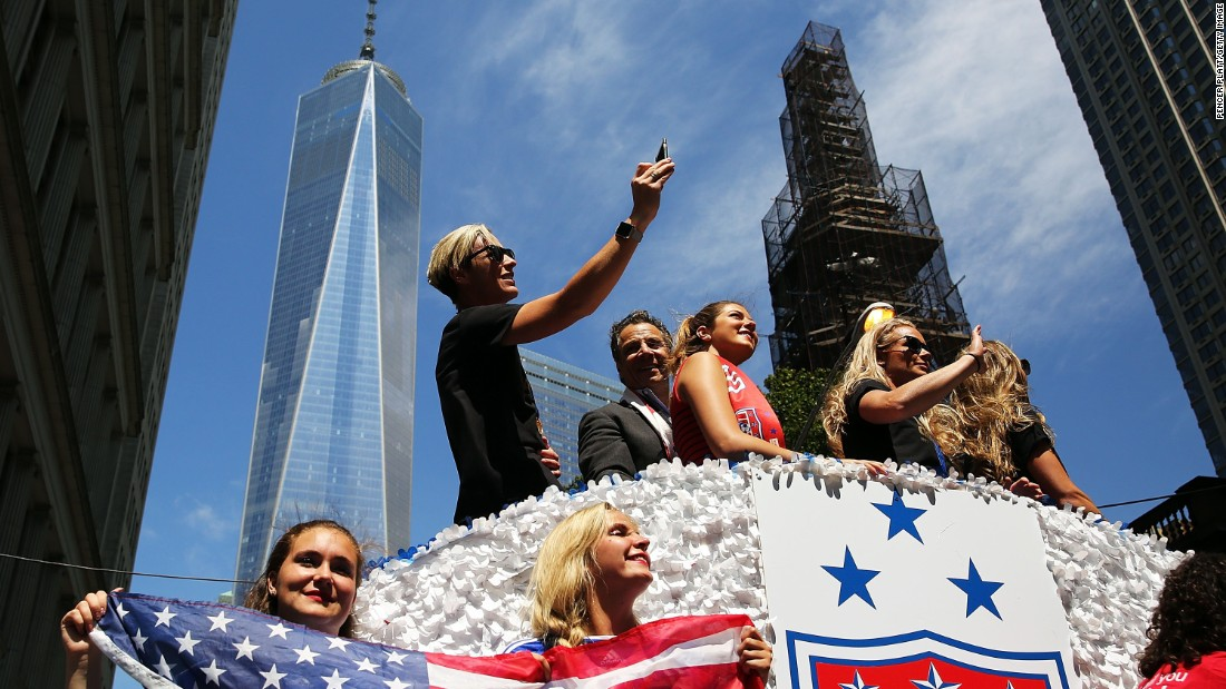 U.S. forward Abby Wambach takes a photo aboard a float. The floats carried the players from Battery Park to City Hall.