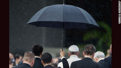 A member of the security detail holds an umbrella over Pope Francis upon his arrival to the Silvio Pettirossi International airport in Asuncion, Paraguay, Friday, July 10, 2015. Francis is now in Paraguay, where he's set to spend three days for the last stop of his South America tour. Paraguay's government declared Friday and Saturday national holidays in honor of the pope's visit. (AP Photo/Victor R. Caivano)