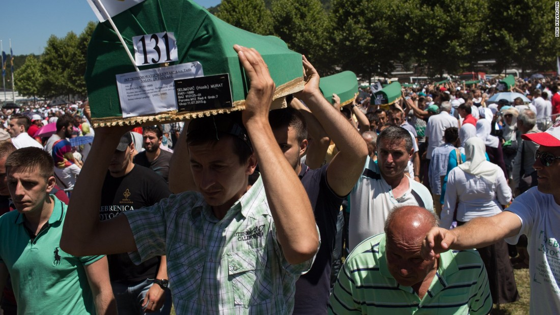 Men carry coffins to be buried.