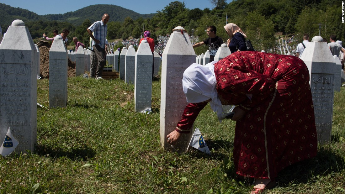 A woman cleans a gravestone in the cemetery.