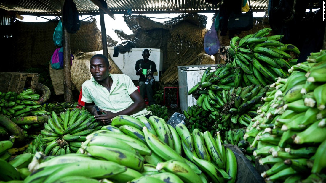 "A South Sudanese market trader sits in his shop where he sells imported bananas from Uganda. Another disease, called ""BXW,"" has nearly destroyed Uganda's banana industry about a decade ago."