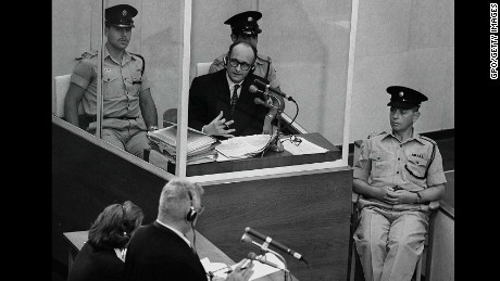 fJERUSALEM, ISRAEL: (FILE PHOTO) Nazi war criminal Adolph Eichmann stands in a protective glass booth flanked by Israeli police during his trial June 22, 1961 in Jerusalem. The Israeli police donated Eichmann's original handprints, fingerprints and mugshot to Jerusalem's Yad Vashem Holocaust memorial ahead of Israel's annual Holocaust remembrance day May 4, 2005 which this year also marks the 60th anniversary of the Nazi's World War II defeat in 1945. (Photo by GPO/Getty Images)