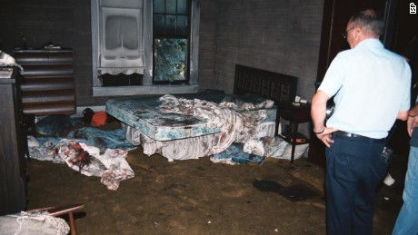 A crime scene photo shows two police officers inspecting the burnt-out bedroom where Karen and Dyke Rhoads had been murdered.