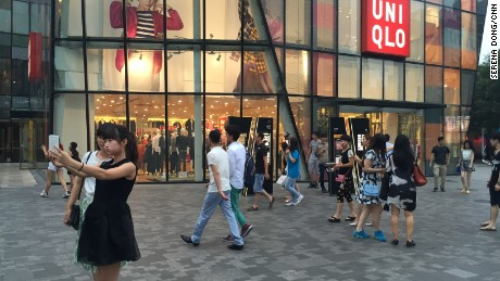 Two women take a selfie outside the Uniqlo store in Beijing on Wednesday, July 15. The store has gained notoriety after a viral sex video was shot inside.