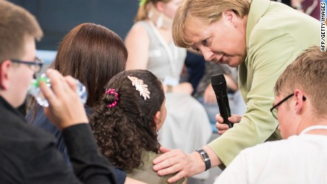 "This Handout photo made available by the German government press office on July 16 2015 shows German Chancellor Angela Merkel (R) comforting a a crying Palestinian girl threatened with deportation on July 15, 2015 in Rostock, northern Germany. Merkel faced a social media storm after the release of a video showing her awkward interaction with the girl threatened with deportation as she addressed a public discussion with teenagers in the northern city of Rostock as part of a government-initiated series called ""Living Well in Germany"". AFP PHOTO / HO / BUNDESREGIERUNG / STEFFEN KUGLER"