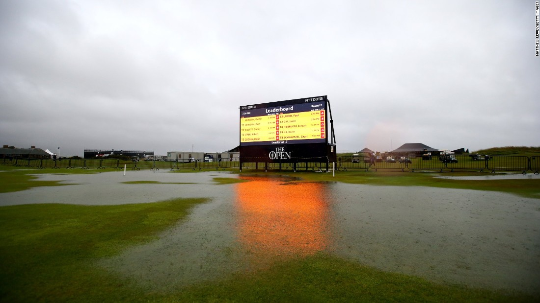 A giant scoreboard illuminates one of the huge puddles that had formed on the Old Course.