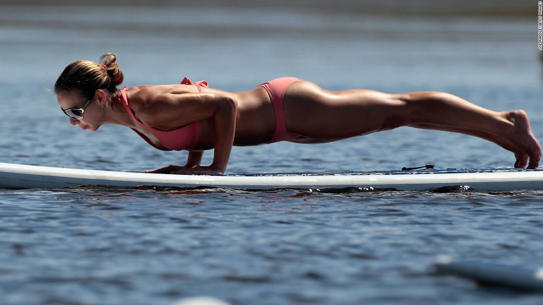 Yoga's explosion in popularity has created a subset of yogi types that populate classrooms in urban centers, which can be intimidating to newbies. This yogi practices a plank pose during a paddleboard yoga session in Miami.