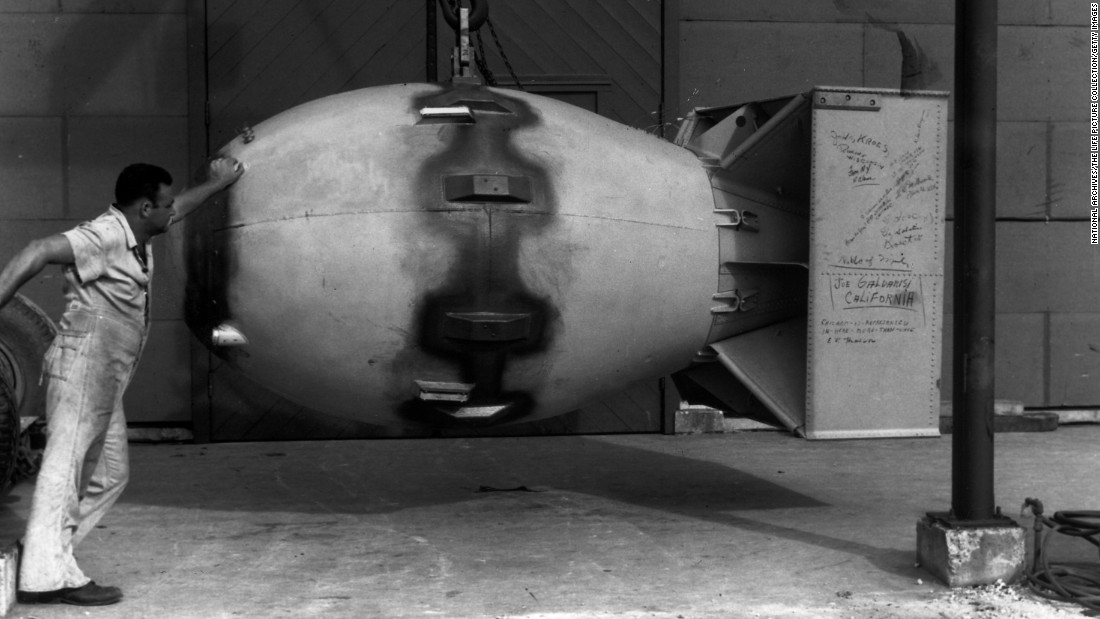 "A worker stands next to an atomic bomb, nicknamed ""Fat Man,"" hours before it was dropped on Nagasaki, Japan, on August 9, 1945."