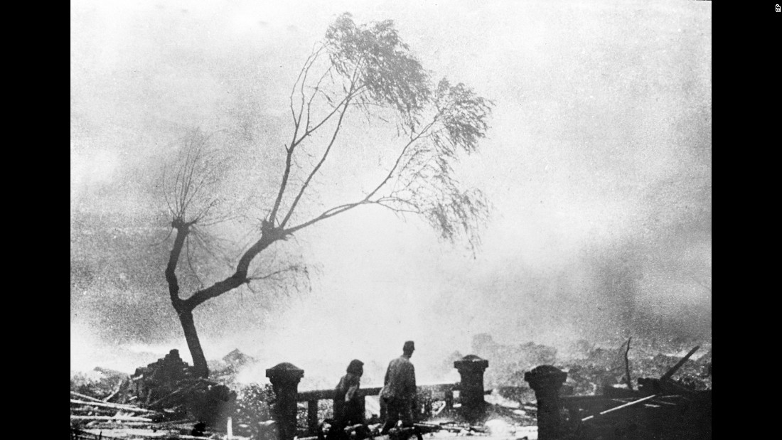 Survivors of the Nagasaki bomb walk through the destruction as fire rages in the background.