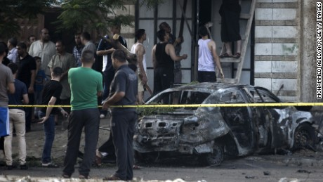 Palestinians gather around a burnt-out car in Gaza City on July 19, 2015, after explosions destroyed five cars in Gaza belonging to members of Hamas and Islamic Jihad, witnesses and a security source said.