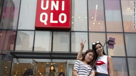 Chinese women take a selfie outside the Uniqlo flagship store, where a video purportedly taken inside one of its fitting rooms shows a couple apparently having sex in Beijing on July 16, 2015.