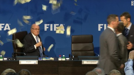Comedian Lee Nelson throws money at Blatter during event