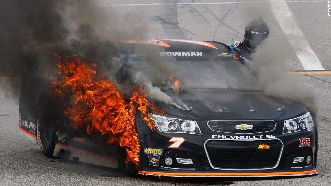 NASCAR driver Alex Bowman climbs out of his car after his front tire caught on fire Sunday, July 19, in Loudon, New Hampshire. Bowman was unharmed.