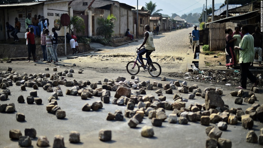 "A man rides past a barricade set up by protesters in Bujumbura on July 21. Animosity against Nkurunziza <a href=""http://www.cnn.com/2015/05/14/world/gallery/burundi-unrest/index.html"" target=""_blank"">boiled over in April</a> when he expressed his intention to run for a third term. There have been protests and a failed coup."