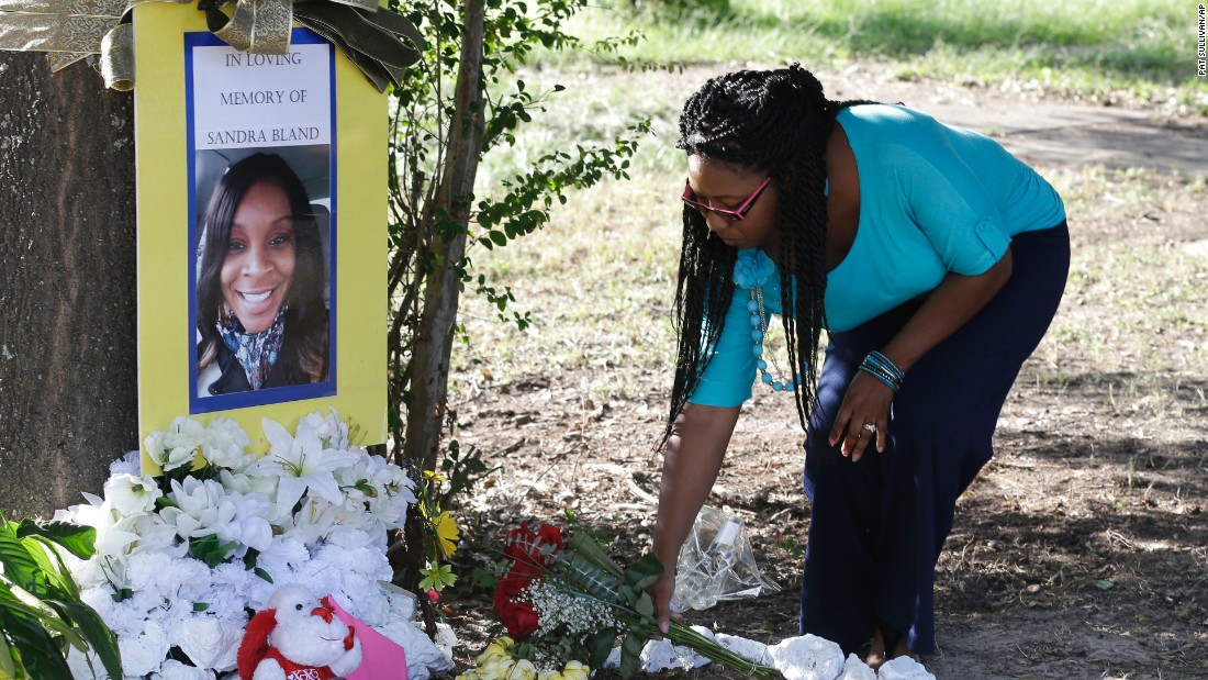 Jeanette Williams places a bouquet of roses at a memorial for Sandra Bland near Bland's alma mater, Prairie View A&M University, in Prairie View, Texas, on Tuesday, July 21.