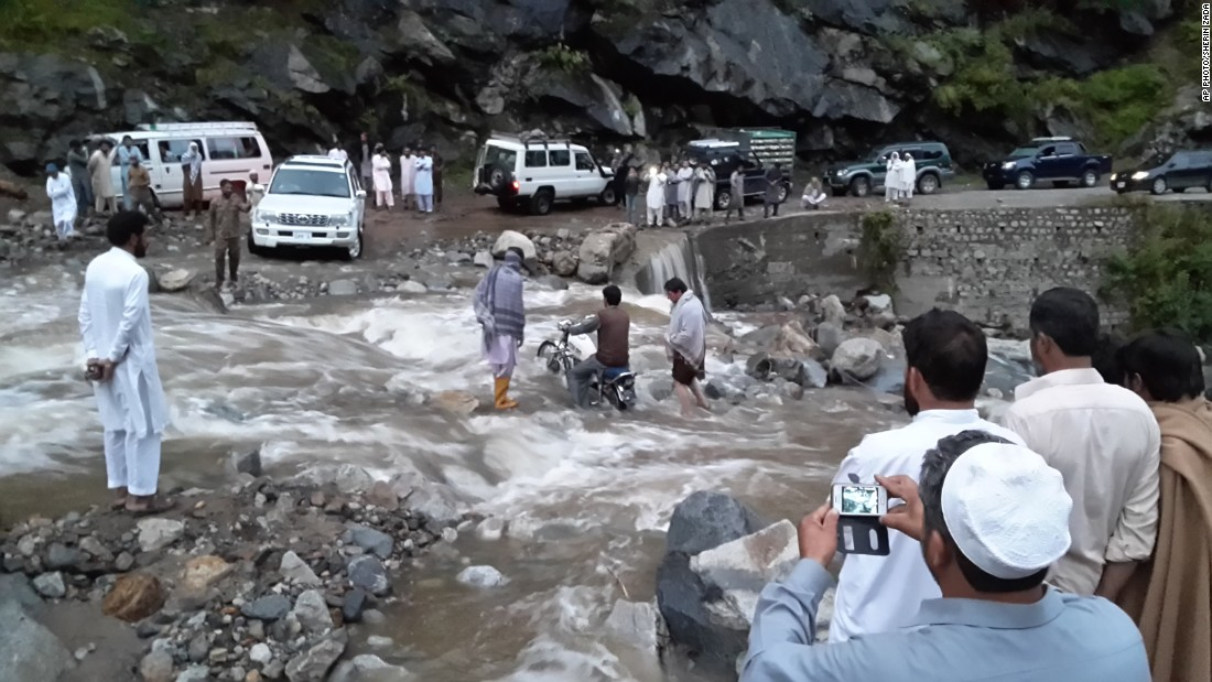 "People stand on a road washed away by heavy flooding in Chitral, Pakistan, on July 21. In a government statement, Prime Minister Muhammad Nawaz Sharif expressed grief and sorrow over the deaths and property damages caused by the floods in Chitral, and instructed the National Disaster Management Authority to coordinate with other departments and reinforce its relief and rescue efforts. The Prime Minister planned to visit the affected areas in Chitral on Tuesday but was ""stuck in Lahore due to bad weather."""