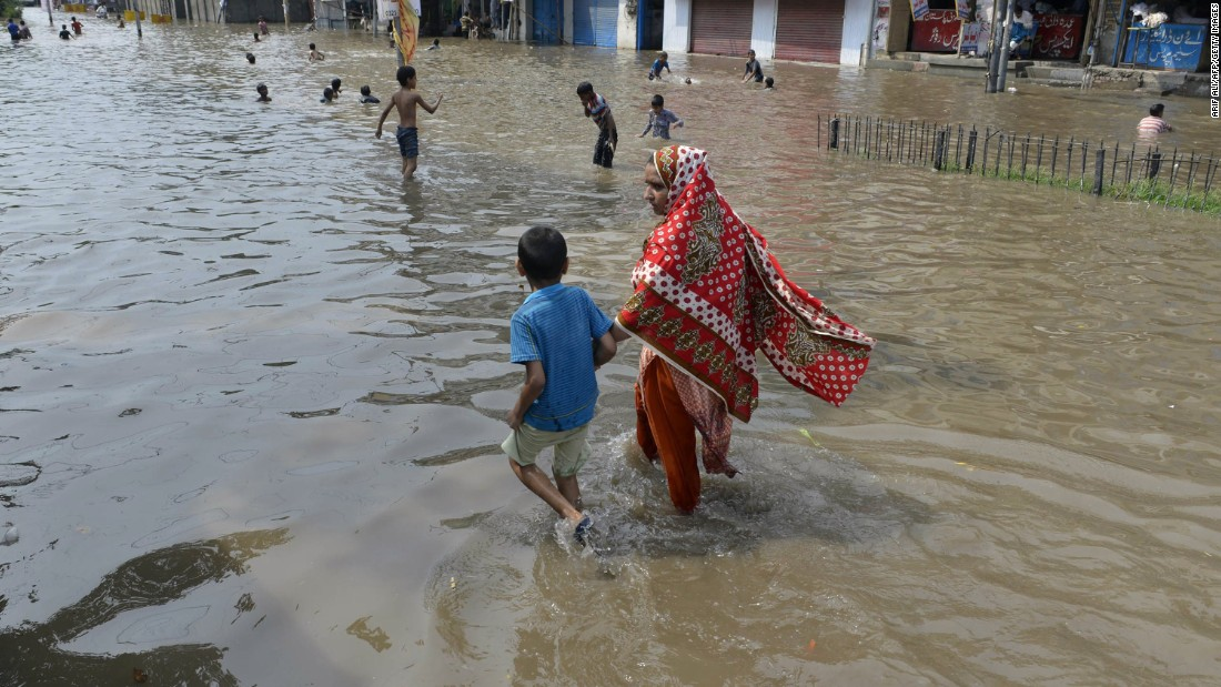 Pakistanis wade through rainwater following heavy monsoon rains in Lahore, Pakistan, on July 21, 2015. This week's flash floods triggered by showers in northern Pakistan have killed at least two people. The Provincial Disaster Management Authority said it was concerned that the region's population has been cut off from the rest of the country with roads and major highways being submerged.
