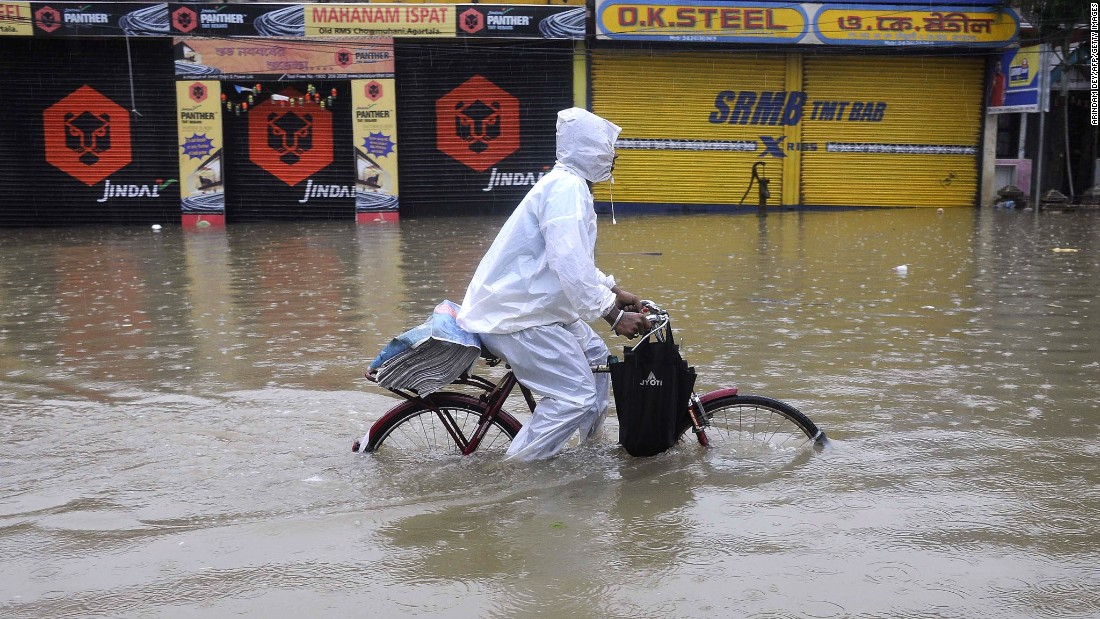 An Indian newspaper distributor pedals his bicycle through a flooded street during a heavy downpour in Agartala, capital of the northeastern Indian state of Tripura, on July 19, 2015.
