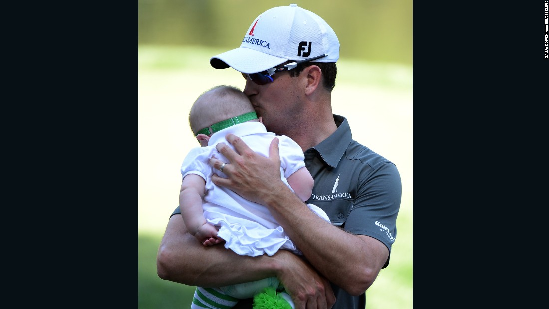 Johnson holds his baby daughter, Abby Jane, during the Par 3 Contest prior to the start of the 2013 Masters Tournament at Augusta.