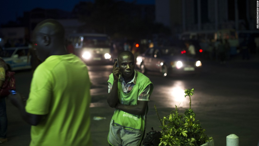 A vendor listens to the news on his cell phone in Bujumbura on Wednesday, July 22. Election results will be announced Friday, with Nkurunziza likely to win a third term. Some opposition groups boycotted the election, and main opposition figure Agathon Rwasa said security forces frustrated his campaign.