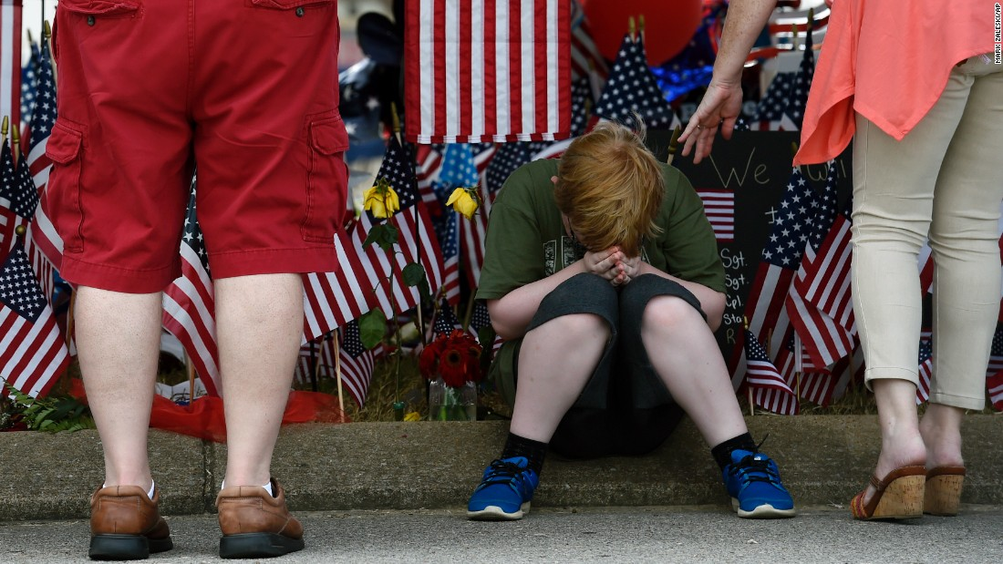 "Nicholas Sisk, 10, bows his head at a makeshift memorial outside a military recruiting center in Chattanooga, Tennessee, on Tuesday, July 21. Authorities say Mohammad Youssuf Abdulazeez, 24, <a href=""http://www.cnn.com/2015/07/16/us/gallery/chattanooga-tennessee-shooting/index.html"" target=""_blank"">opened fire on the recruiting station</a> on July 16 before moving to a U.S. Navy facility seven miles away. At the Navy facility, Abdulazeez fatally wounded four U.S. Marines and a Navy sailor before being killed in police gunfire."