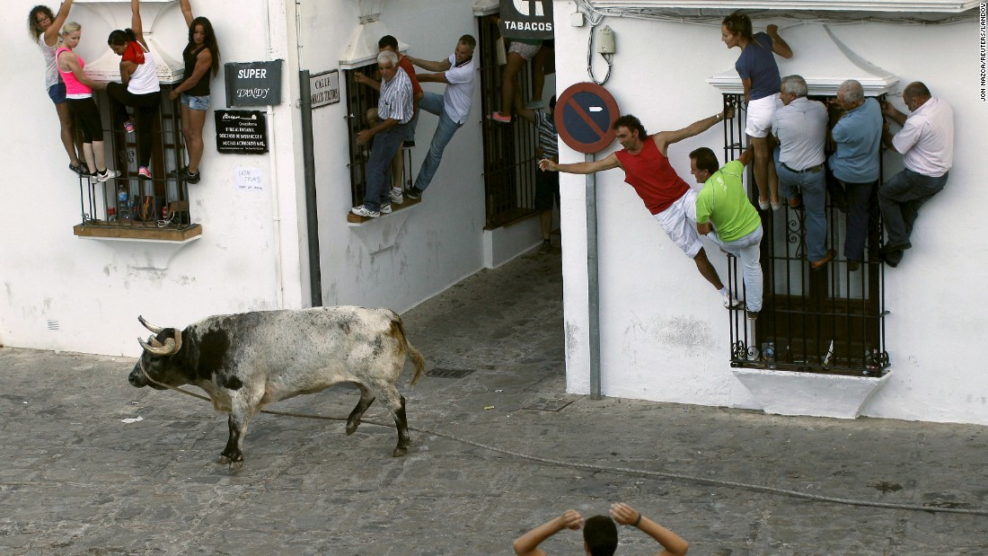 People in Grazalema, Spain, avoid a bull during the Toro de Cuerda festival on Monday, July 20. During the festival, a long rope restrains bulls as they run through the village's streets.