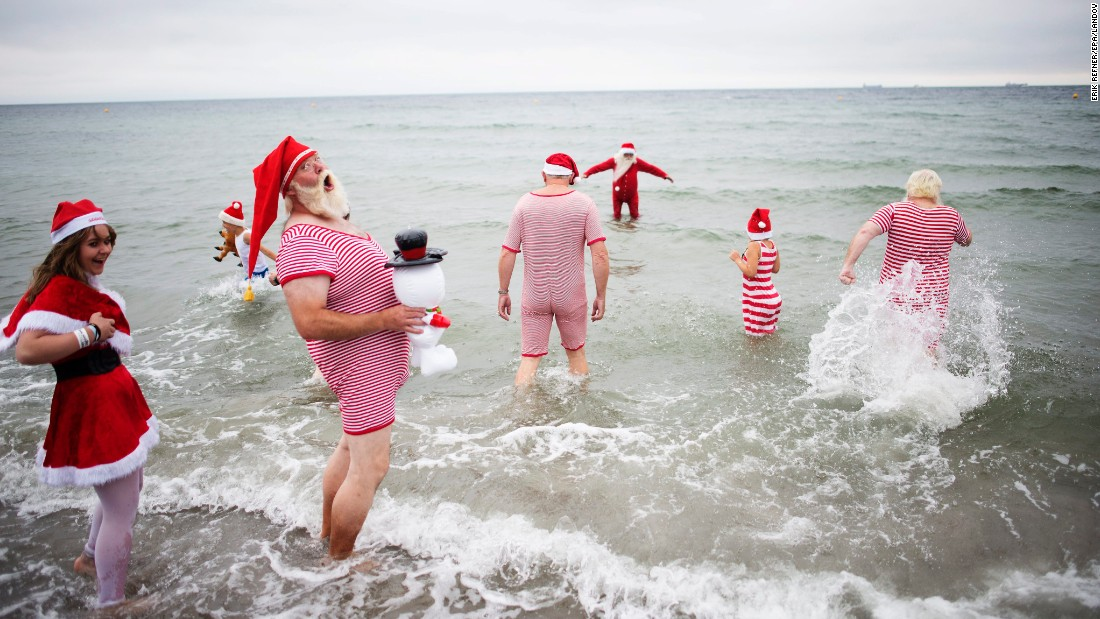Participants from the World Santa Claus Congress enter the water at Bellevue Beach, north of Copenhagen, Denmark, on Tuesday, July 21.