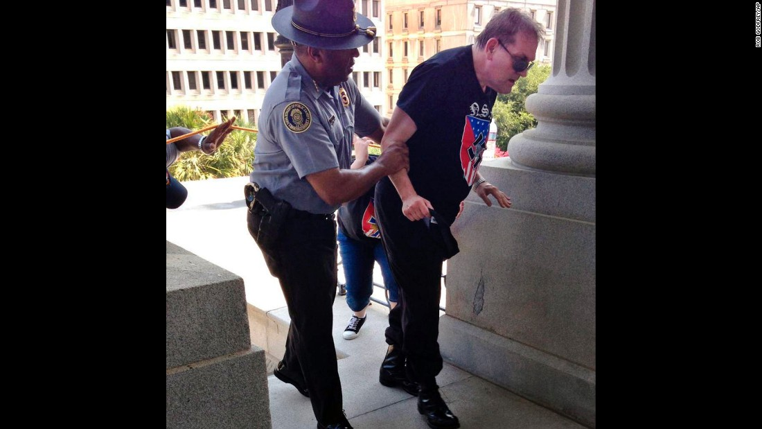 "As white supremacists were protesting the removal of the Confederate flag from the South Carolina State House grounds, Public Safety Director Leroy Smith helped a man who was struggling from the heat on Saturday, July 18. The photo <a href=""http://www.cnn.com/2015/07/19/us/black-officer-white-supremacist-feat/"" target=""_blank"">spread through social media</a> after Rob Godfrey, deputy chief of staff to South Carolina Gov. Nikki Haley, tweeted the photo with the caption, ""not an uncommon example of humanity in SC."""