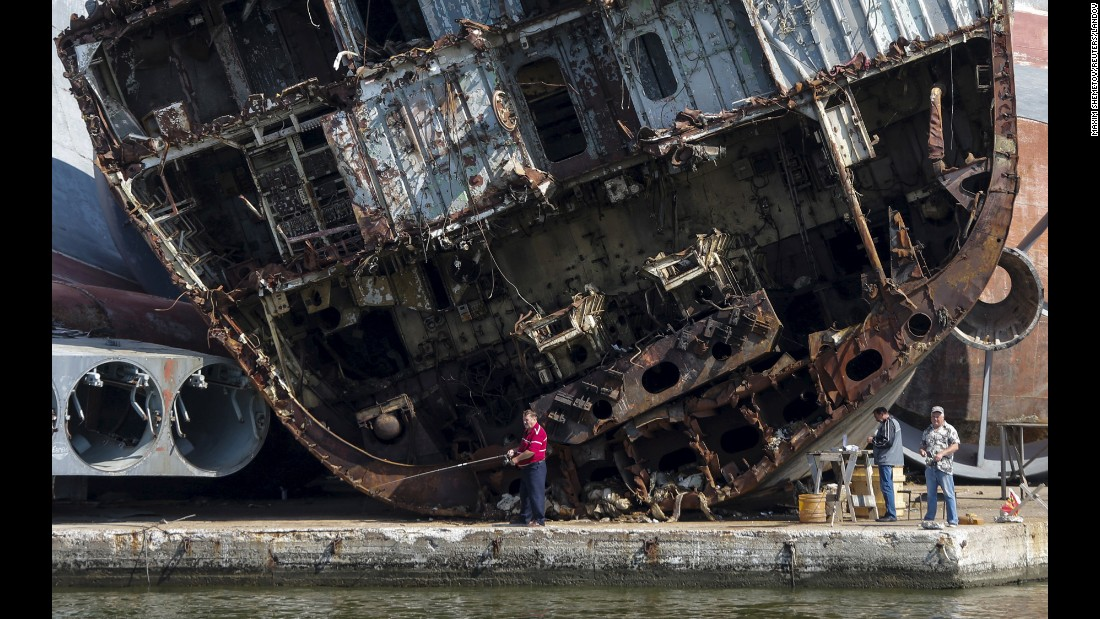 Men fish in front of ship remains at the Russian fleet base in Baltiysk on Sunday, July 19.