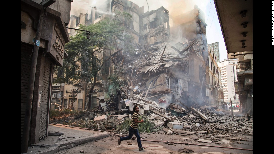 A man runs past the remains of a burning building in downtown Cairo on Monday, July 20. According to local reports, at least 17 fire engines were dispatched to the scene.